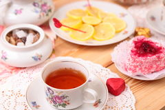 Warm cup of tea, lemon and sweets Royalty Free Stock Photos