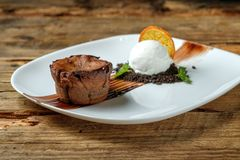 Warm dessert chocolate cake Fondant. Served on plate with scoop of ice-cream, mint, crumbs, orange on a wooden background royalty free stock photos