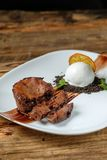 Warm dessert chocolate cake Fondant. Served on plate with scoop of ice-cream, mint, crumbs, orange on a wooden background royalty free stock images