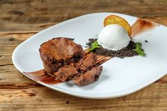 Warm dessert chocolate cake Fondant. Served on plate with scoop of ice-cream, mint, crumbs, orange on a wooden background royalty free stock image