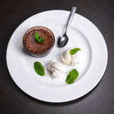 Warm dessert chocolate fondant lava cake served with vanilla ice cream balls and mint on white plate. Famous French dessert on dar Stock Photos
