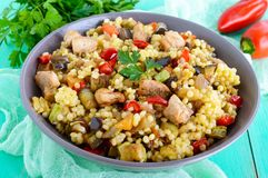 Warm dietary salad from baked vegetables zucchini, sweet pepper, eggplant, onion, chicken and couscous. Tabbouleh - Eastern snack Royalty Free Stock Photography
