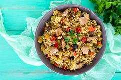 Warm dietary salad from baked vegetables zucchini, sweet pepper, eggplant, onion, chicken and couscous. Tabbouleh - Eastern snack Royalty Free Stock Image