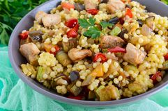 Warm dietary salad from baked vegetables zucchini, sweet pepper, eggplant, onion, chicken and couscous. Tabbouleh - Eastern snack Royalty Free Stock Images