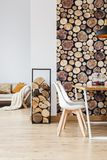 Room inspired by autumn woodland. Warm dining room decor inspired by autumn woodland with simple furniture, firewood and logs wallpaper Royalty Free Stock Photos