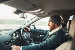 Warm dressed bearded man driving modern auto. Inside car view. Winter weather driving stock images