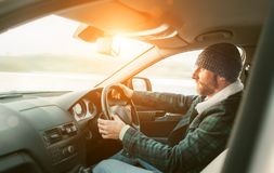 Warm dressed Bearded Man driving a new modern auto. Inside car v royalty free stock images
