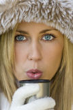 Warm Drink. A stunningly beautiful young blond woman wrapped up warm and blowing onto a warm drink Royalty Free Stock Photos