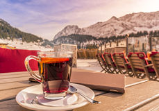 Warm drink and restaurant menu on table in alpine decor. Image with a hot drink and a restaurant menu, on a wooden table, on a sunny winter day, mountains in the Royalty Free Stock Photography