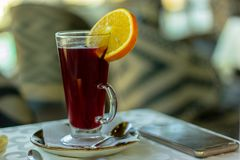 Warm drink with an orange on the plate and phone royalty free stock photos