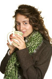 Warm Drink on a Winter Day. Curly haired beautiful young lady in a green scarf drinking coffee Royalty Free Stock Images