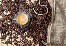 Warm Espresso cup over wooden table full of coffee beans. royalty free stock photo