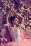 Young woman in pink ballet tutu surrounded by flowers stock photos