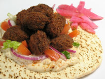 Warm Falafels and Pita Bread. A delicious portion of falafels served on top of a pita bread with hummus, lettuce, tomato, red onions, and a side of turnips royalty free stock image