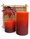Warm Fall Spa candels. Red and orange fall coloured spa candels with oriental bamboo details and autumnal leaf Royalty Free Stock Images