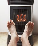 Warm feet in front of fire Royalty Free Stock Images