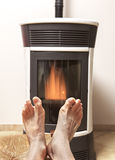 Warm feet in front of fire Stock Images