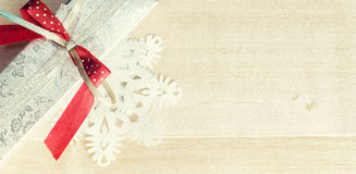 Warm filtered gift and paper snowflakes on wood. Christmas siver Royalty Free Stock Photo