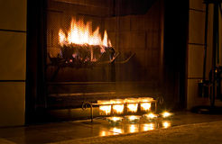 Warm fireplace. Romantic fireplace with candles burning in front Stock Photography