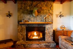 Warm fireplace in living room with a deer head mounted on stone fireplace. stock images