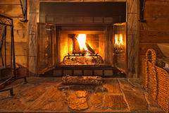 Warm Fireplace. With the screen pulled back you can clearly see the warm fire in the stone fireplace Royalty Free Stock Photo