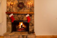 Warm fireplace with wreath, candelabras and two Christmas stockings in the family home stock photos