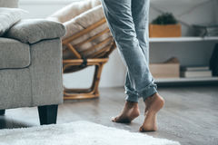 Warm floor concept. Close-up of female legs stepping by hardwood floor at home Stock Images