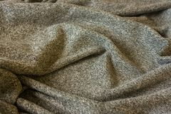 Warm fluffy grey blanket. Texture of material with folds. Warm fluffy grey cozy blanket. Texture of material with folds stock images