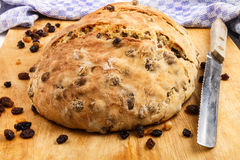 Warm, fresh home baked raisin bread on a wooden board with bread. Knife and kitchen towel in the background Stock Photo