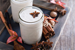 Warm frothy milk with spices. Warm frothy milk with syrup and winter spices Stock Photo