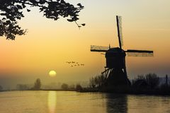 Warm and frozen windmill sunrise. Geese flying over a beautiful early morning and warm Kinderdijk sunrise on windmills and loading platform nearby Alblasserdam Royalty Free Stock Image