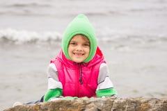 Warm gekleidetes Mädchen mit dem Lächeln, das heraus von hinten einen Felsen gegen den Hintergrund des Meeres späht Lizenzfreies Stockfoto
