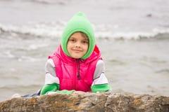 Warm gekleidetes Mädchen schaut heraus von hinten einen Felsen gegen den Hintergrund des Meeres am kalten bewölkten Tag Stockfoto
