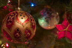 The Warm Glow of Christmas. Hand crafted and painted globes and star shaped Christmas tree ornaments hung on a Noble Fir tree Stock Photos