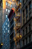 Warm glow of sunlight shining on a fire escape on the front of a Stock Images