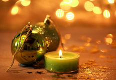 Warm glowing Christmas decoration background. With a burning green candle and baubles surrounded wth scattered gold stars against a backdrop bokeh of sparkling stock photos