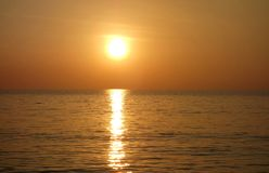 Warm Golden Tropical Ocean Sunset with Large Sun. A classic sunset image of a high golden sun with a warm but bright radiant large sun radiating and reflecting royalty free stock photography