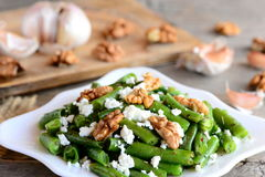 Warm green bean salad. Easy green string beans salad with cottage cheese, peeled walnuts, garlic and spices on a white plate Royalty Free Stock Photos