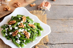 Warm green bean salad recipe. Balsamic green beans salad with creamy cheese, crunchy walnuts, garlic and spices on a plate Royalty Free Stock Photos