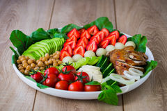 Warm grilled chicken salad with vegetables and fruits. Warm grilled chicken salad with strawberries, melon balls, onion rings, tomatoes, mangold, peas, white Royalty Free Stock Photos
