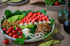 Warm grilled chicken salad with vegetables and fruits. Warm grilled chicken salad with strawberries, melon balls, onion rings, tomatoes, mangold, peas, white Royalty Free Stock Photography