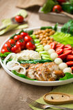 Warm grilled chicken salad with vegetables and fruits. Warm grilled chicken salad with strawberries, melon balls, onion rings, tomatoes, mangold, peas, white Stock Image