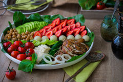 Warm grilled chicken salad with vegetables and fruits. Warm grilled chicken salad with strawberries, melon balls, onion rings, tomatoes, mangold, peas, white Royalty Free Stock Image