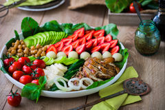 Warm grilled chicken salad with vegetables and fruits. Warm grilled chicken salad with strawberries, melon balls, onion rings, tomatoes, mangold, peas, white Stock Photo