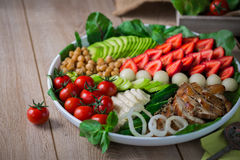 Warm grilled chicken salad with vegetables and fruits. Warm grilled chicken salad with strawberries, melon balls, onion rings, tomatoes, mangold, peas, white Royalty Free Stock Photo