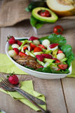 Warm grilled chicken salad with vegetables and fruits. Warm grilled chicken salad with strawberries, melon balls, onion rings, tomatoes, mangold, peas, white Stock Images