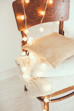 Warm home decor. A stack of white and beige pillows and blankets with string lights on vintage wooden chair. Cozy interior details, soft and warm home decor Royalty Free Stock Photography