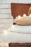 Warm home decor. A stack of white and beige pillows and blankets with string lights on vintage wooden chair. Cozy interior details, soft and warm home decor Royalty Free Stock Photo