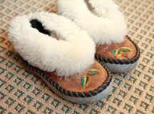 Warm house slippers. A pair of warm house shoes on a rug royalty free stock photo