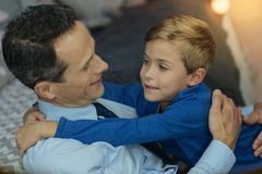 Positive father embracing his son. Warm hugs. Attractive boy opening mouth while looking at his daddy and feeling happiness Royalty Free Stock Photos